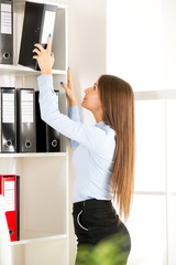 Young Businesswoman In Front Of Shelves With Binders