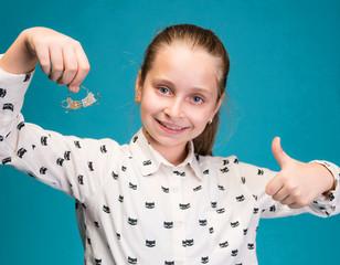 Happy girl holding dental braces