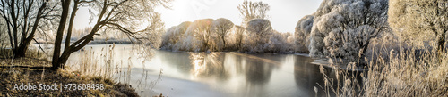 Panorama of the frozen lake and snow-covered trees - 73608498