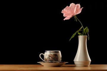Pink rose in white vase and coffe cup isolated black bacground