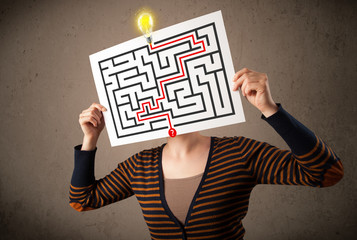 Woman holding a paper with a labyrinth on it in front of her hea