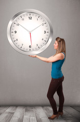 Attractive lady holding a huge clock