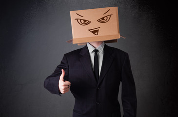 Businessman gesturing with a cardboard box on his head with evil