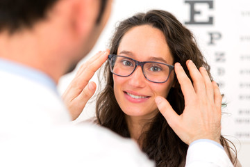Young attractive woman trying glasses w optician