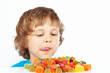 Little boy looking at colored jelly candies on white background