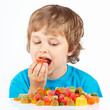 Little boy eating jelly candies on a white background