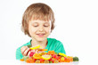 Little boy with sweets and jelly candies on a white background