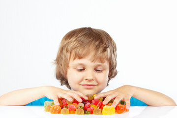Little blonde boy with colored jelly candies on white background