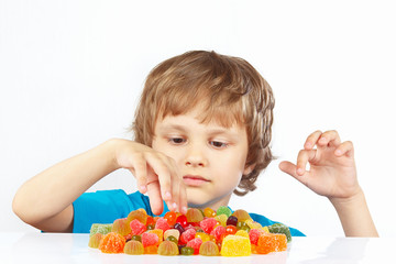 Little blonde child with jelly candies on a white background