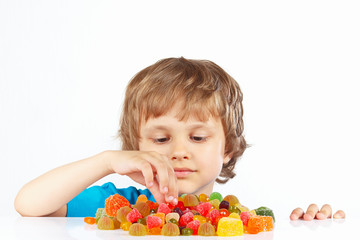 Little blonde child with candies on a white background