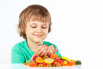 Little blonde child with colored jelly candies