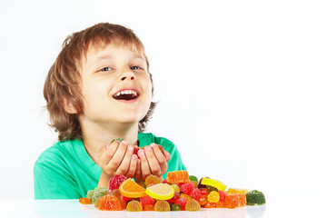 Smiling child with jelly candies on a white background