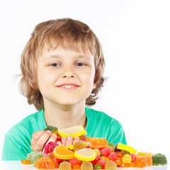 Little child with sweets and candies on a white background