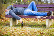 Man with beer bottle sleeping on a bench in the park