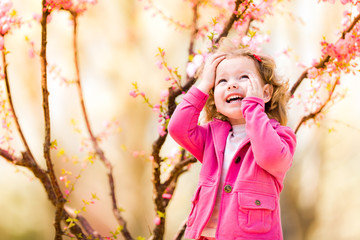 Beautiful baby girl in blooming jasmin tree branches