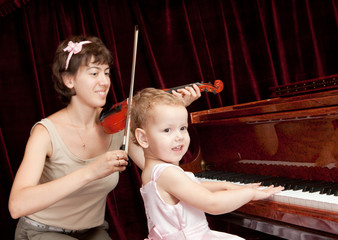 Mother and daughter playing piano and violin