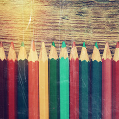 Row of colored drawing pencils closeup on old desk. Vintage styl