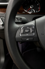 Control buttons on steering wheel. Car interior detail.