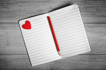 Black and white photo of open notebook with red heart and pencil