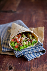 Tortilla wrap with tomatoes, cucumbers, lettuce