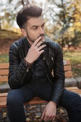 young fashion man enjoying his cigarette