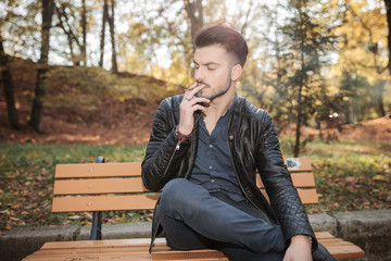 fashion man sitting on a bench in the park