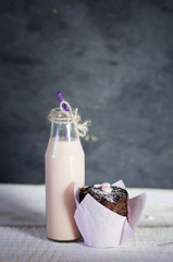 Retro bottle with pink  milk cocktail  and chocolate cupcake.