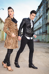 fashion couple standing and holding hands