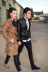 young fashion couple walking forward, holding hands.