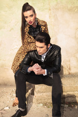 fashion man sitting while his girlfrined is leaning on him