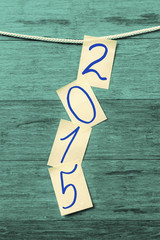 Pages on the rope with 2015 digits against wooden background