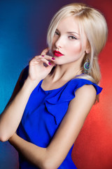 beautiful women blonde with red lips in blue dress in the Studio