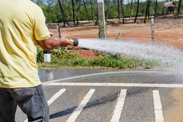 Man holding big water hose to clean the road