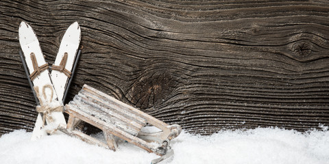 Wintersport Ski und Schlitten vor Holzwand