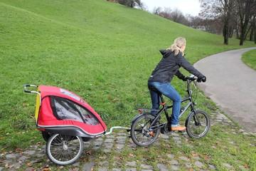 Mutter auf Fahrrad mit Kinderanhänger und E-Bike