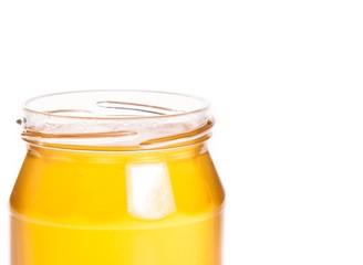 closeup of opened honey jar on white background