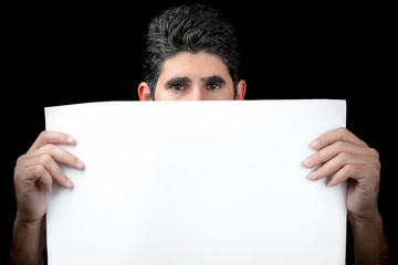 Young man hiding behind a white banner