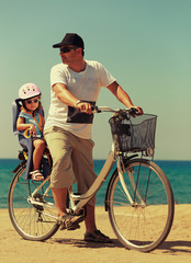 Father and daughter biking on the beach on blue sea background
