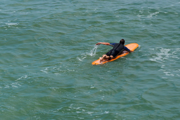 Surfer man over a yellow board