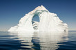 A lone iceberg floats in a still, deep blue sea.