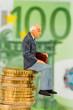 Rentner sitzt auf Geldstapel