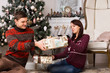 Young man giving his girlfriend a Christmas gift