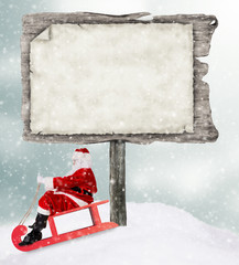 Santa Claus on sledge with wooden sign