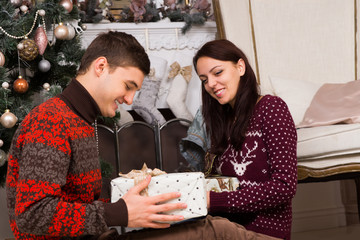 Smiling Couple with Presents Near Christmas Tree