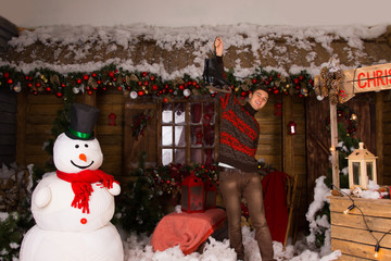 Man Holding Skates Up at Christmas Decorated House