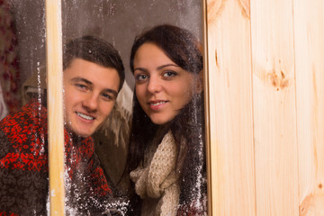 Smiling young couple looking through a window