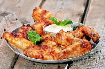 Baked chicken wings on wooden table