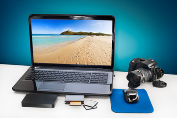 Post production desk with laptop, digital camera.
