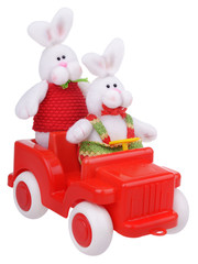 White stuffed rabbits in red car