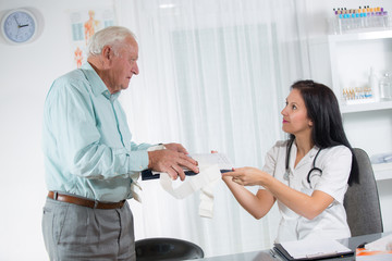 Doctor talking to her male senior patient at office